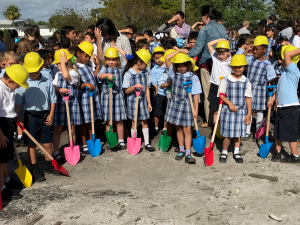 Children in hard hats holding shovels
